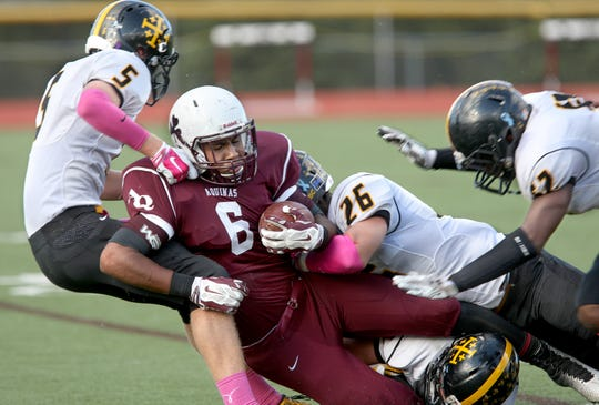 McQuaid's Matt Szuromi, left,  tackles Aquinas' Taylor Riggins with the help of McQuaid teammate Jake Zimmer in the second quarter at Aquinas Institute on Saturday, Oct. 11, 2014. Riggins and Zimmer are now teammates at the University at Buffalo.