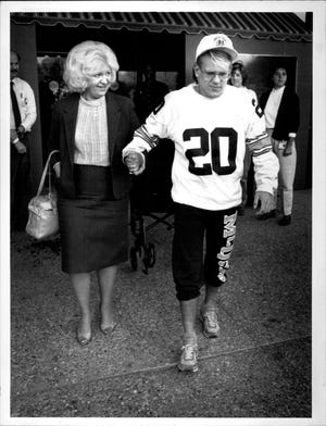 McQuaid football player Terry Wolak, walks out of Strong Memorial Hospital with his mother, Mary Wolak, on Nov. 18, 1988. Terry was hurt in a football game and partially paralyzed.