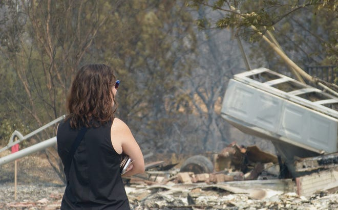 A woman gazes at what's left of a Kilkee Drive home in the Mary Lake neighborhood in Redding.