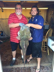 Mike Stanley,left, and Corbin Wake hooked this 53-pound catfish from the Hornersville Swamp Wildlife Area on their trotline.