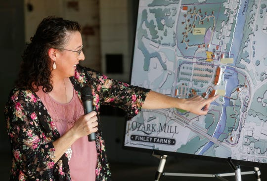 Kris Dyer points to where the old Riverside Bridge will be placed  as part of Bass Pro Shops Ozark Mill project along the Finley River in Ozark on Wednesday, Aug. 1, 2018.