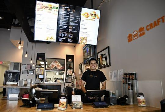 Burgerim employee Thomas Jimenez works the cash register at the new Visalia restaurant, located on Mooney Boulevard.