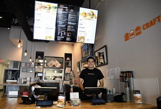 Burgerim employee Thomas Jimenez works the cash register at the new Visalia restaurant, located on Mooney Boulevard.