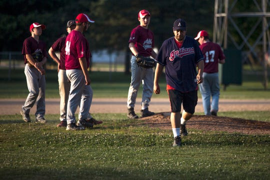 Jose Olvera talks to players for the Abby Broncos, the baseball team that he coaches, before their game in Abbotsford, Wis., July 11, 2018.