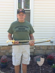 Paul Missett holds the Kenneth Russom's sword before shipping it to Russom's home in Florida.