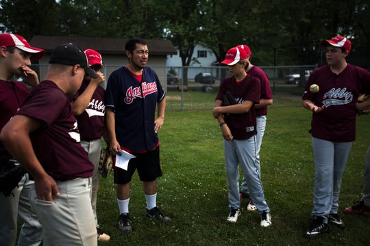Jose Olvera talks to the Abby Broncos, the baseball team that he coaches, before a game. His two sons Marco, 15, and Nickolas, 13, play on the team.