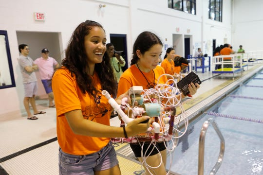 """Students participating in """"Camp CryptoBotÓ Cybersecurity Camp at Pace University try to retrieve coded messages from a downed drone in a make believe scenario at the pool at Pace University on Aug. 1, 2018.  The program is part of the Pace UniversityÕs Seidenberg School of Computer Science and Information Systems cybersecurity camp for high school students from the trip-state area, which is which is funded by the National Security Agency and the National Science Foundation to help prepare young people for careers in the field of cybersecurity."""
