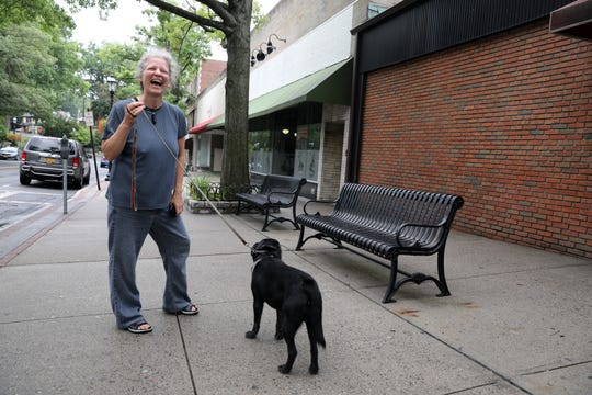 """Tarrytown resident Lynne Lori Sylvan, 54, with her dog Chester Chestnut, chats with an acquaintance after discussing developers' plans to build a mixed-use complex on North Broadway in Tarrytown August 1, 2018 beside the proposed site.  """"I don't mind housing if they're going to have affordable housing. If they are going to have 225 housing units, I like at least half to be affordable,"""" she said."""