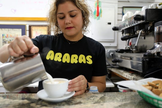 Co-owner Marina Cardozo makes a cappuccino at Araras Coffee & More, where they sell Brazilian coffee and treats in White Plains, July 31, 2018.