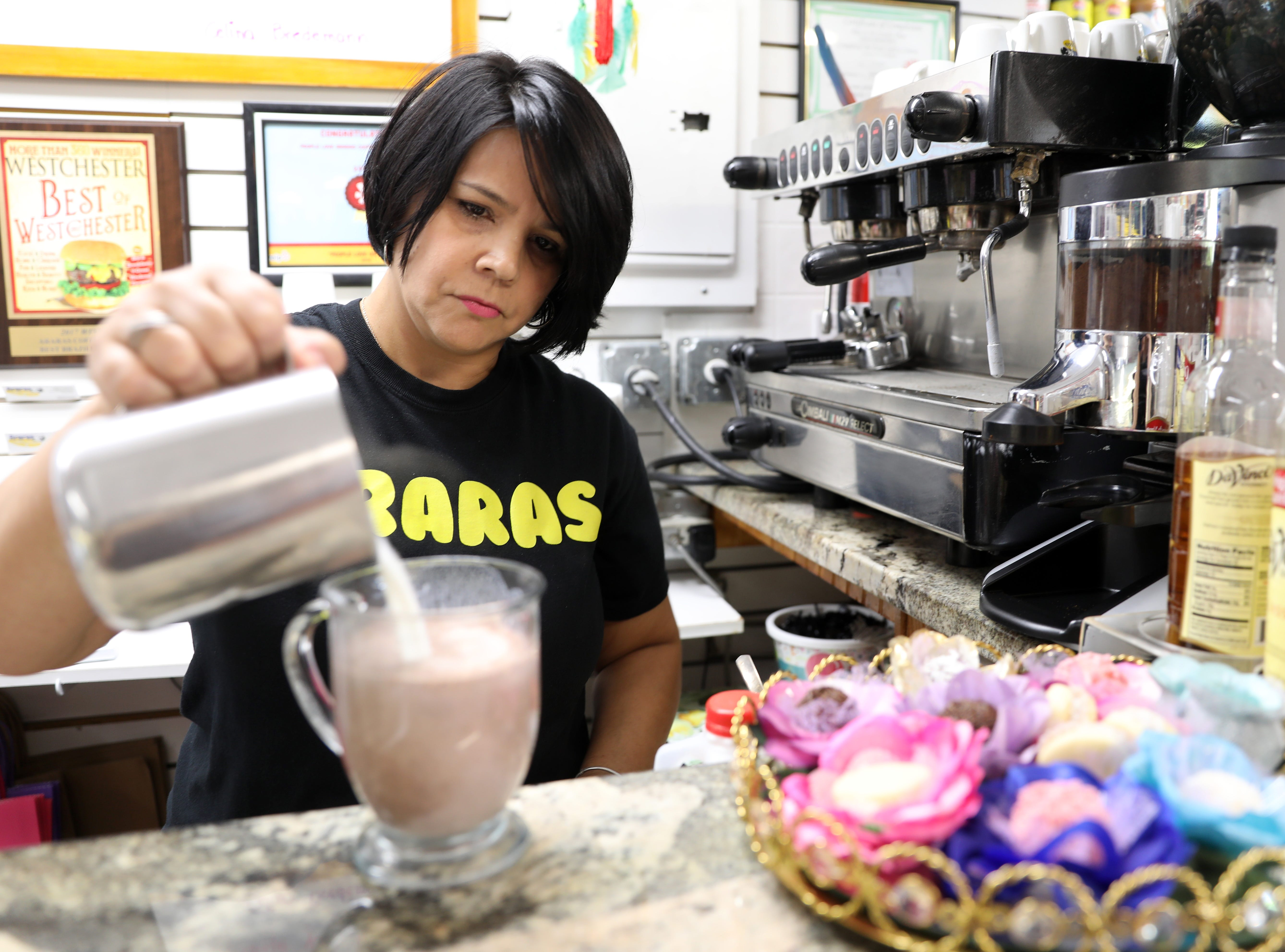 Co-owner Celina Bredemann makes hot chocolate at Araras Coffee & More, where they sell Brazilian coffee and treats in White Plains, July 31, 2018.