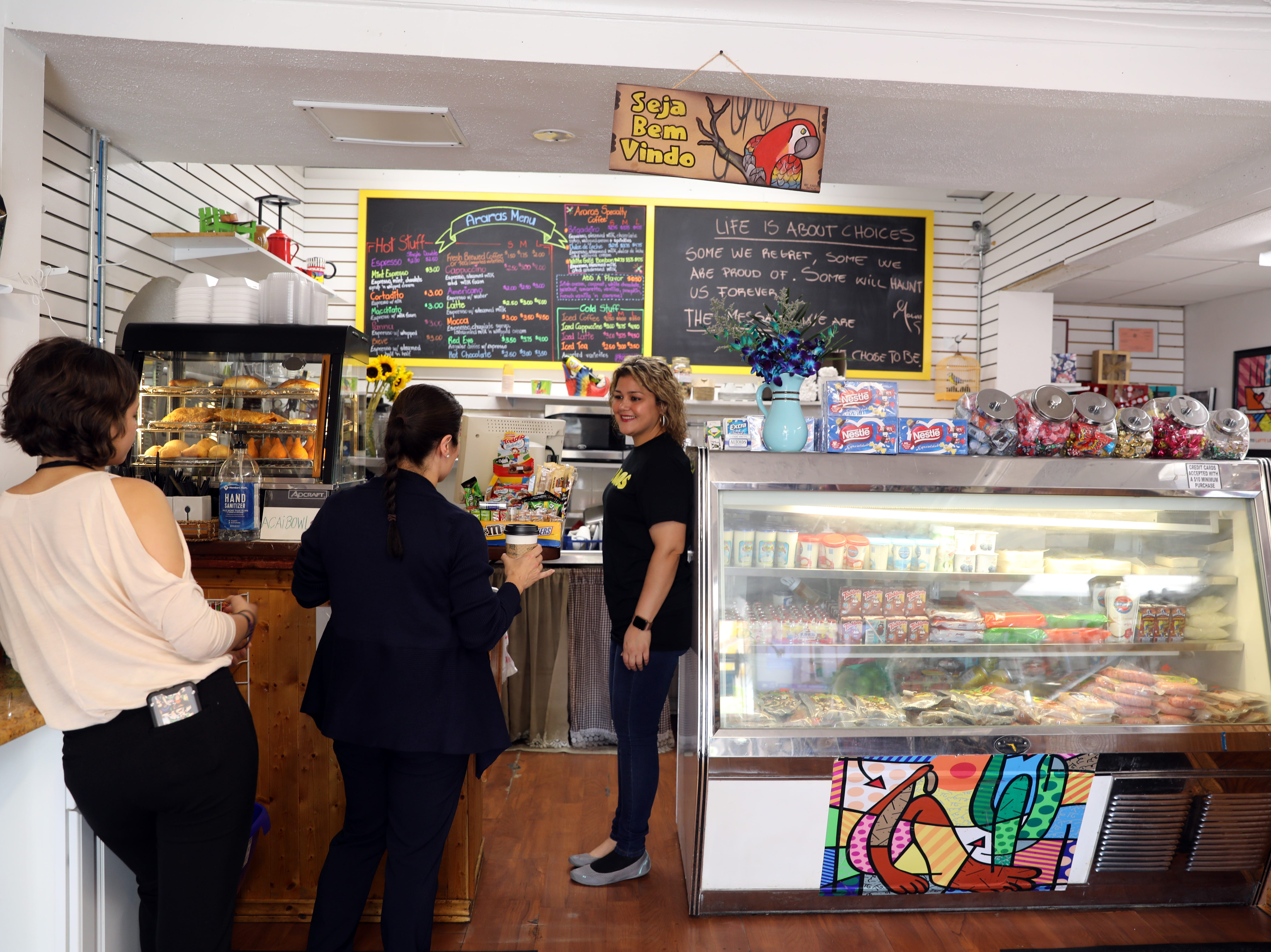 Co-owner Marina Cardozo chats with a customer at Araras Coffee & More in White Plains. The cafe sells Brazilian coffee and treats.