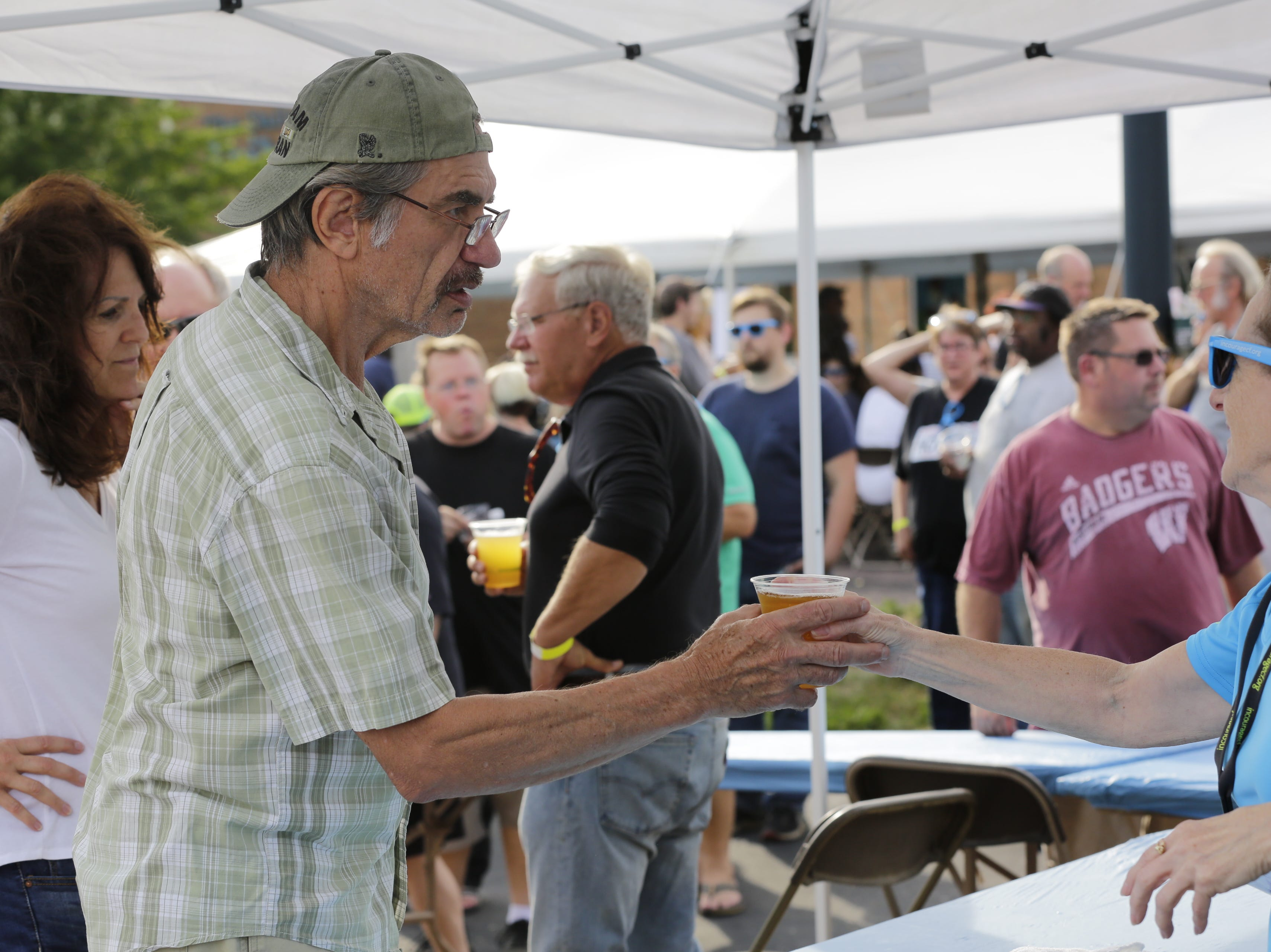 Bob Jazdzewski orders a beer at the Wisconsin Rapids community picnic on First Avenue South and Johnson Street Wednesday, August 1, 2018.