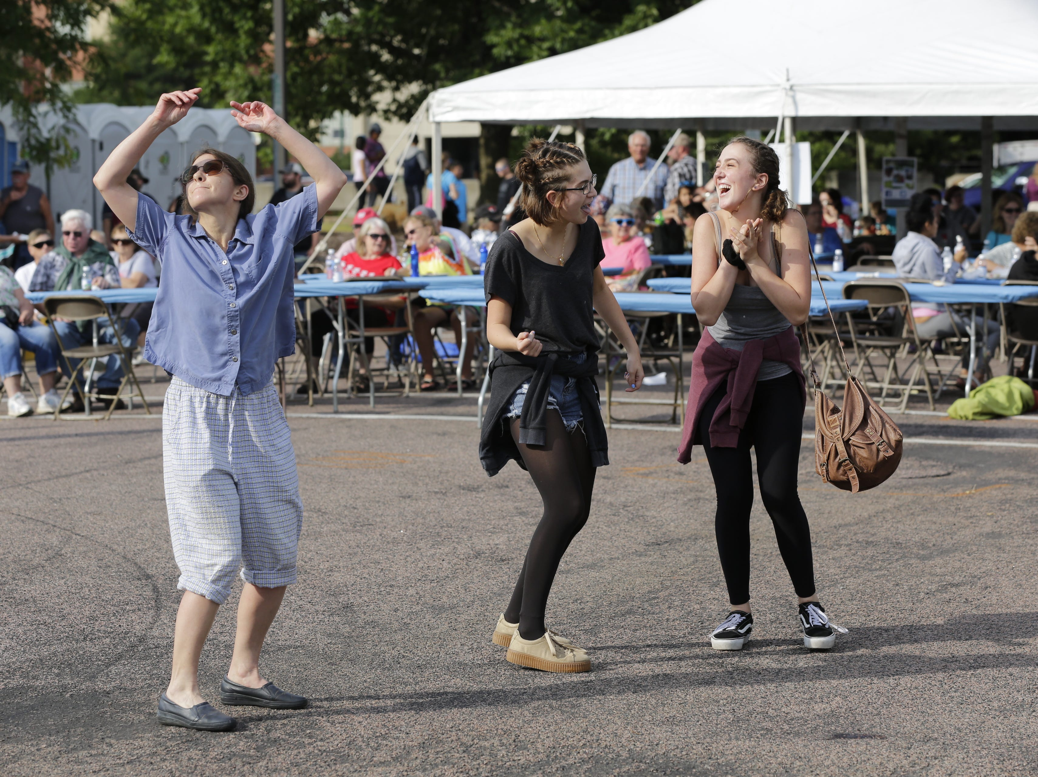 Violet Gutowski, left, Allison Braun, 17 and Lydia Page, 17, dance to the band Southbound at the Wisconsin Rapids community picnic on First Avenue South and Johnson Street Wednesday, August 1, 2018.