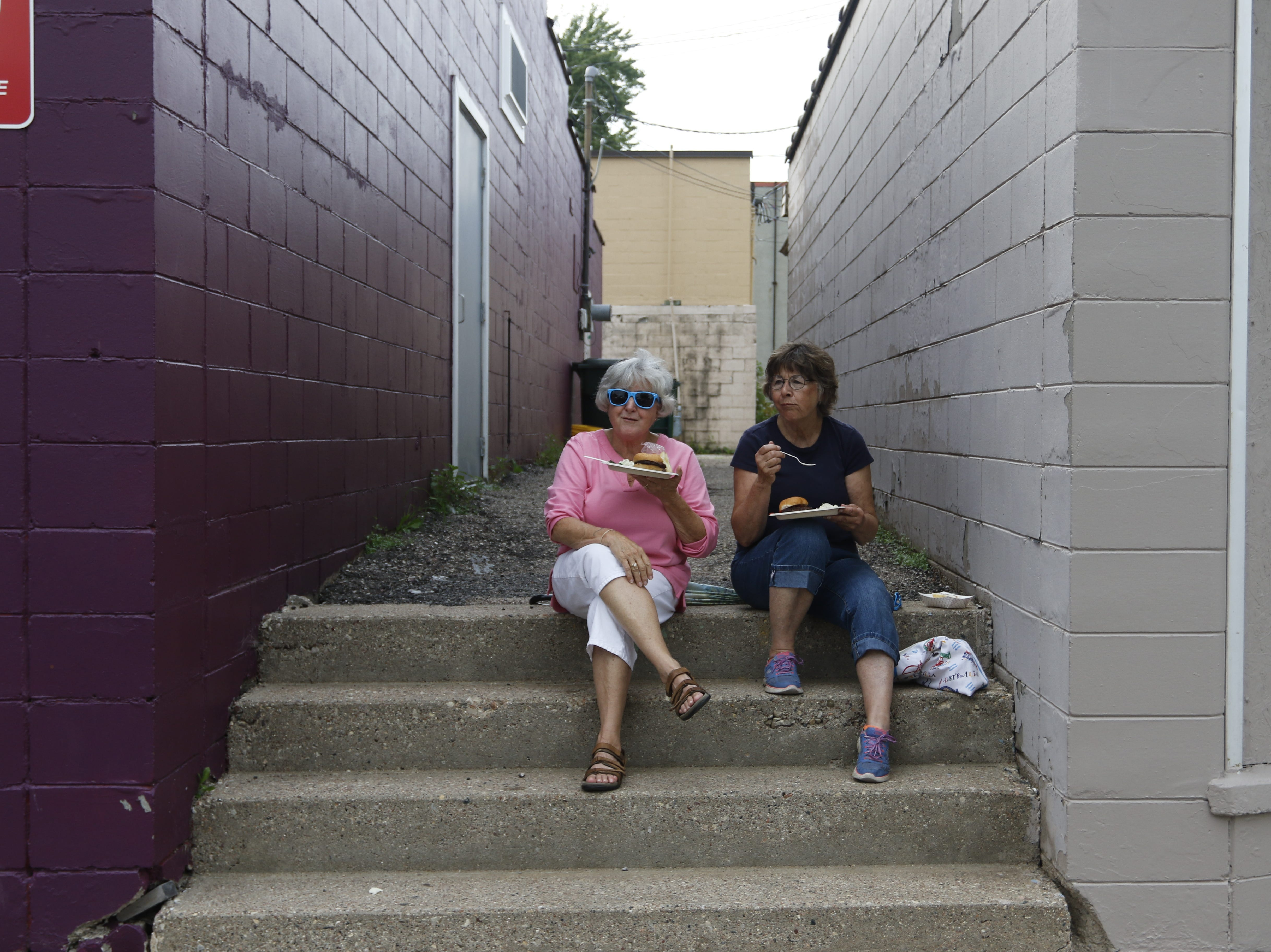Helen Sparks, left and Dodi Saumer eat and watch the line of people waiting for corn at the Wisconsin Rapids community picnic on First Avenue South and Johnson Street Wednesday, August 1, 2018.