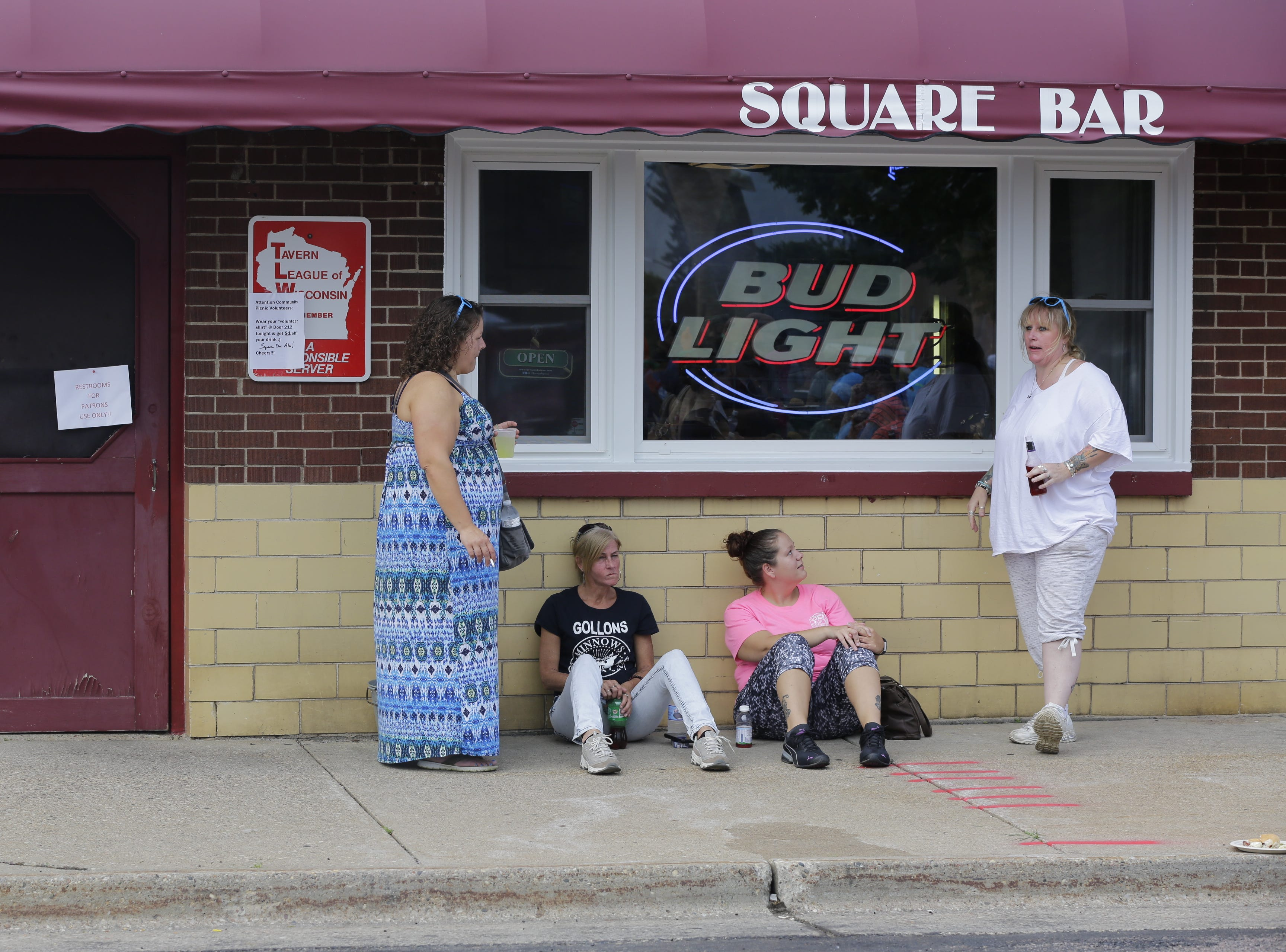A group talks outside of Square Bar during the Wisconsin Rapids community picnic on First Avenue South and Johnson Street Wednesday, August 1, 2018.