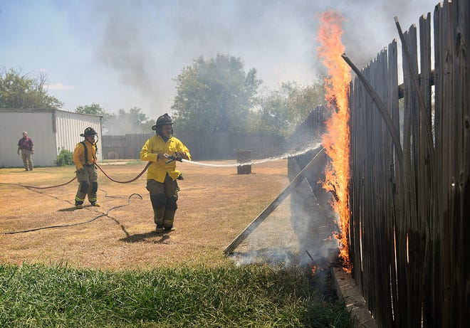 Wichita Falls firefighters work to protect the property of Debbie Wade onn the 1800 block of FM 171 Wednesday afternoon as a large brush fire threatened several homes in the area.