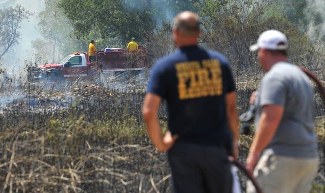 Several local fire agencies work to control a grass fire on FM 171, Wednesday afternoon.