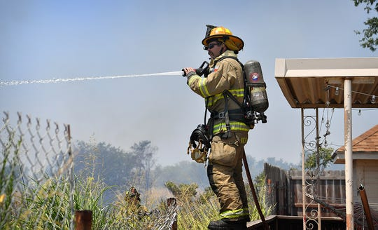 In this file photo, Wichita Falls Fire Lt. Cory Lindemann stops part of a brush fire from advancing as several homes in the 1800 block of FM 171. Fire and police employees of Wichita Falls will get a 5 percent pay increase in the 2019-2020 fiscal year.