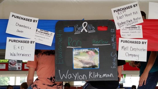 Evansville 4-H member Waylon Klitzman hung signs showing the buyers for his pig Roo at the Rock County 4-H Fair on July 27. Through the sale, Klitzman was able to donate more than $10,000 to Beat Nb.