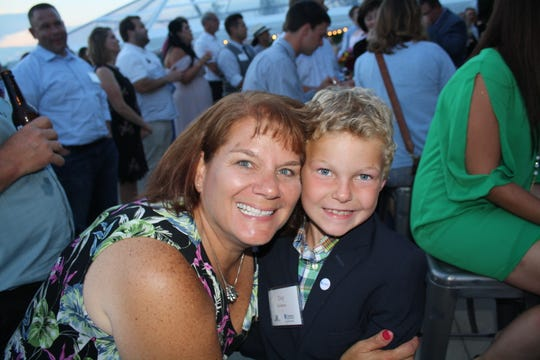 Lori Olson shares a smile with Troy Rockman, who gave a moving testimonial about how Children's Hospital of Wisconsin repaired a hole in his heart at the July 28 Garden Party.