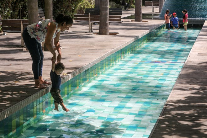 A woman refreshes her son in a fountain in the eastern part of Lisbon, Portugal, on August 1, 2018.