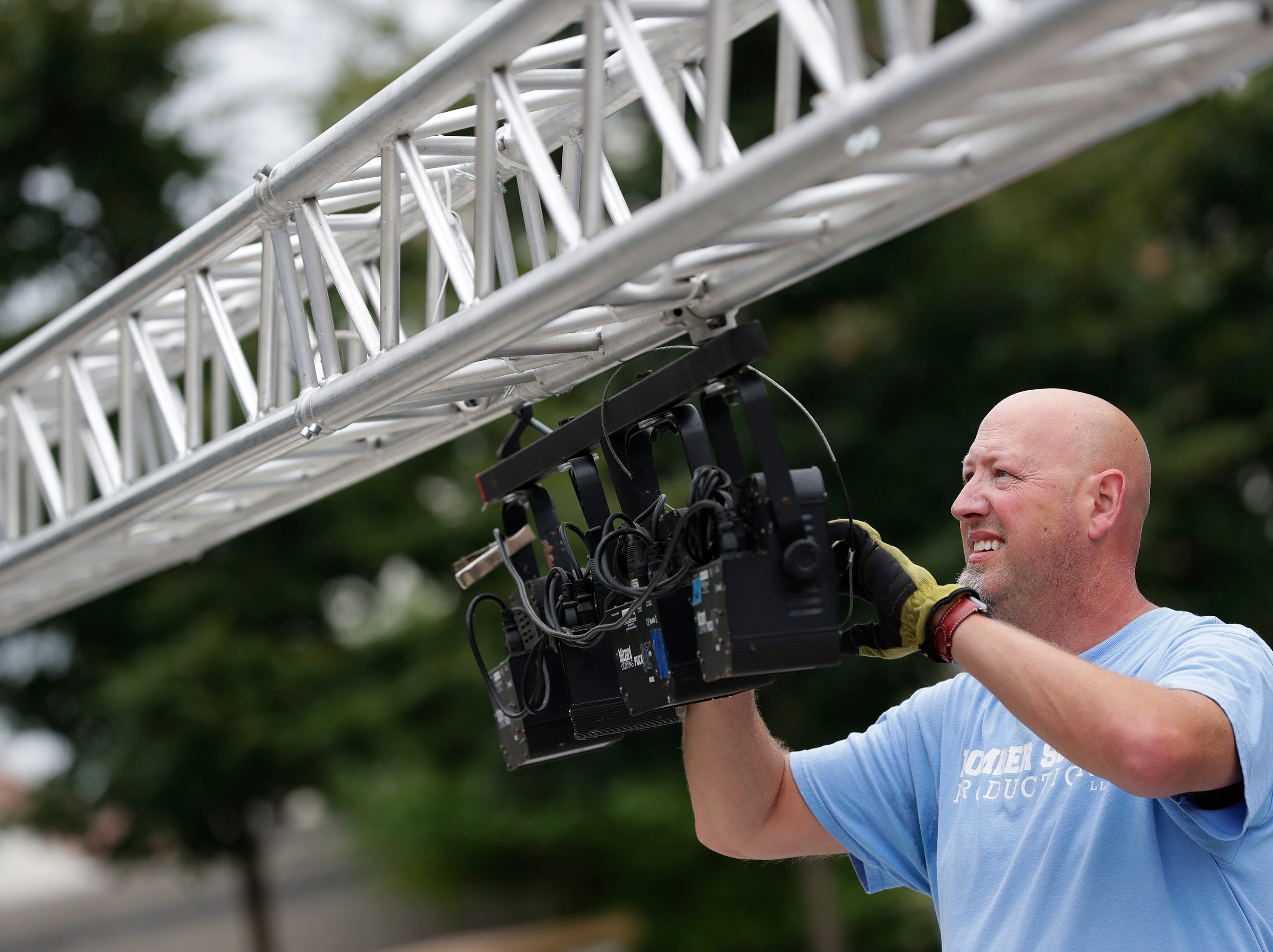 Brian Meixl, an employee with Bomber Sound Producitions out of Appleton, sets up lighting for the Houdini Plaza stage during the Mile of Music Thursday, August 2, 2018, in Appleton, Wis.  Dan Powers/USA TODAY NETWORK-Wisconsin