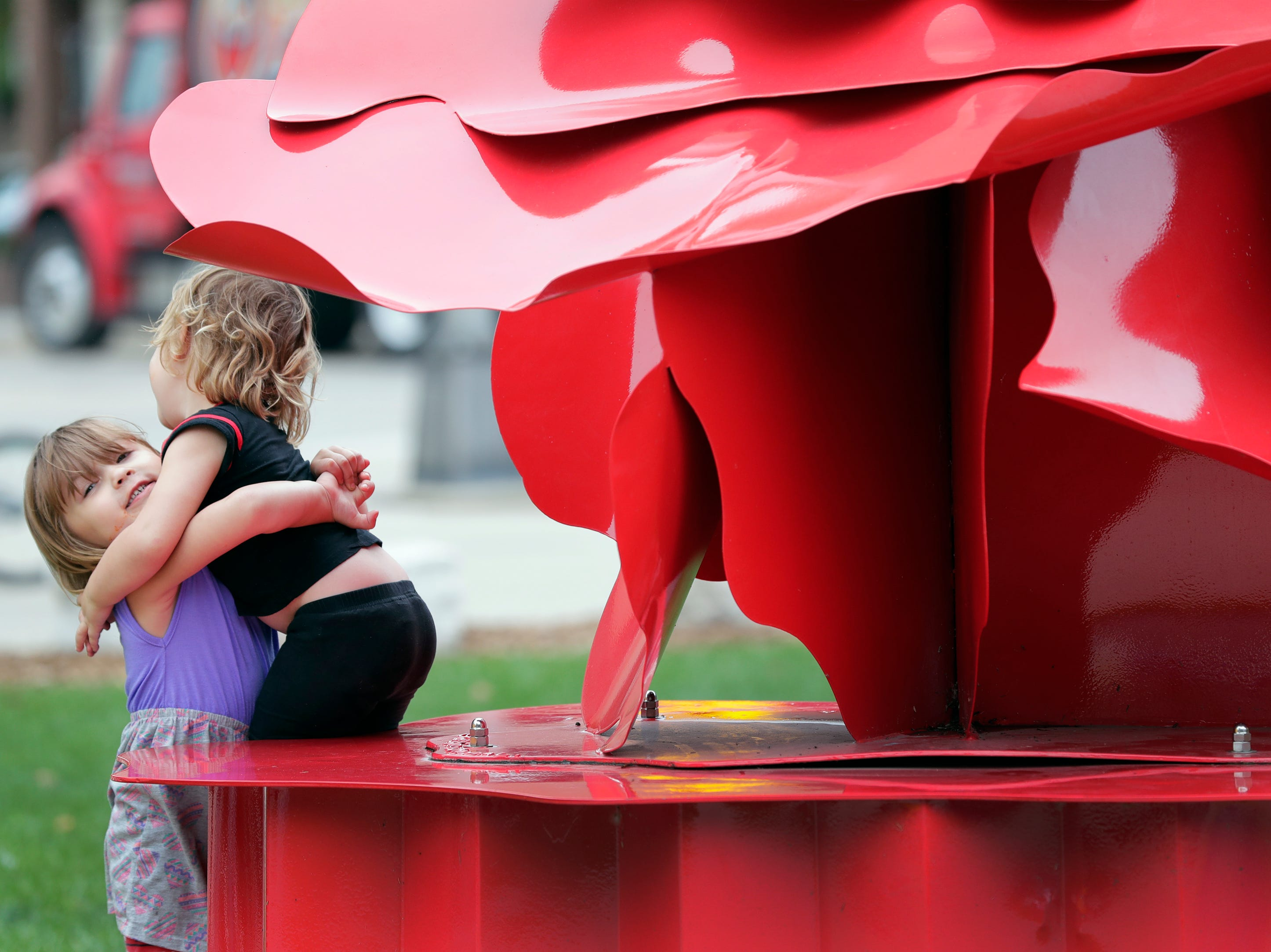 Callie Hooyman, 3, left, helps her twin sister Rylee Hooyman as they play on a sculpture in Houdini Plaza during the Mile of Music Thursday, August 2, 2018, in Appleton, Wis.  Dan Powers/USA TODAY NETWORK-Wisconsin