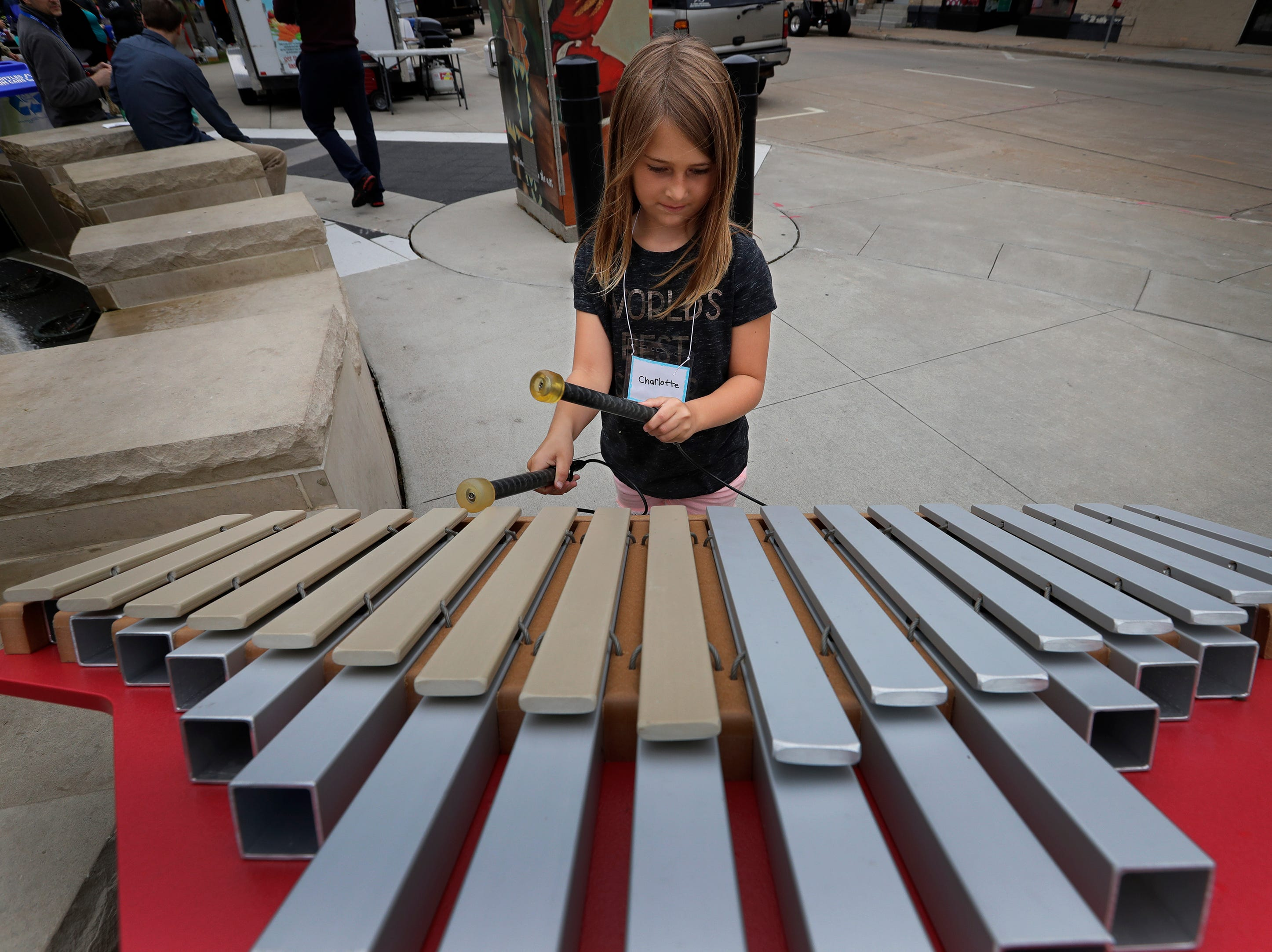 Charlotte Beyer, 7, of Appleton plays an instrument at Houdini Plaza during the Mile of Music Thursday, August 2, 2018, in Appleton, Wis.  Dan Powers/USA TODAY NETWORK-Wisconsin
