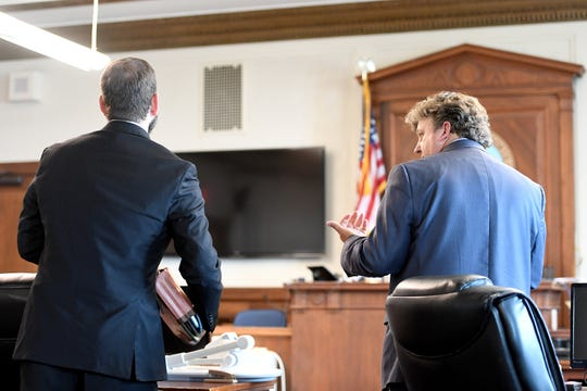 Buncombe County attorney Brandon Freeman, left, and John Sutton, the attorney representing Marcus Hyatt, speak with a judge about needing to postpone a hearing about the release of police body camera footage from the day Hyatt was detained at the Buncombe County Courthouse on Tuesday, July 31, 2018.