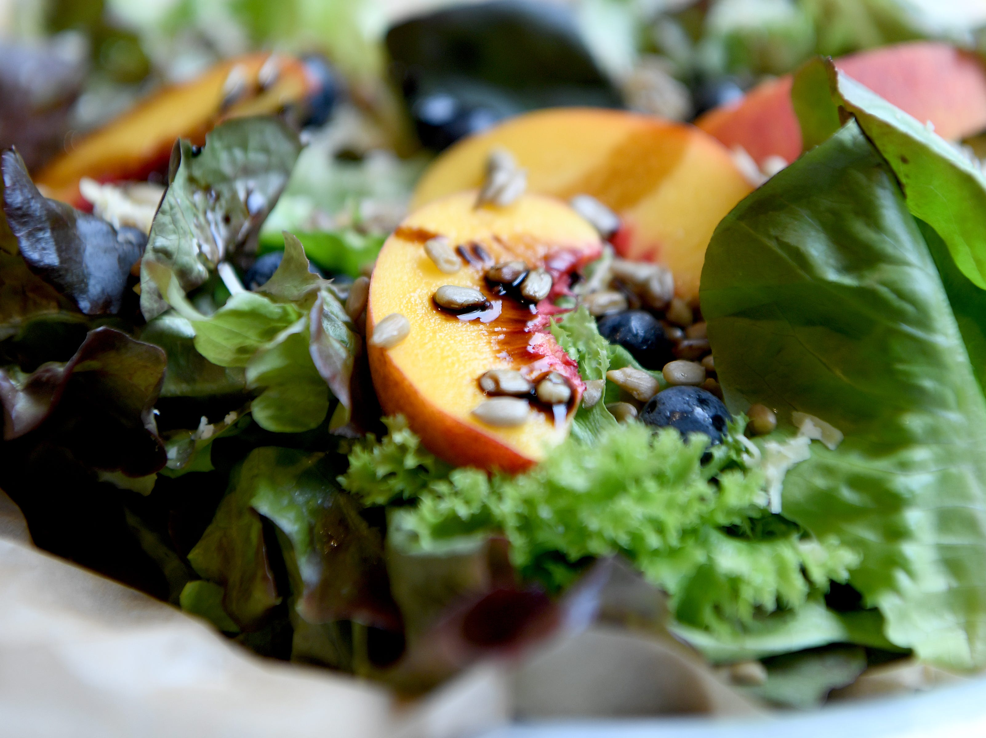 The farmers salad at HomeGrown West has mixed Greens, peaches, farmstead cheese, sunflower seeds and is topped with a balsamic reduction.