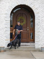 Todd Jordan, with his police K9 Bear, walk outside of the home of Subway restaurant spokesman Jared Fogle, Tuesday, July 7, 2015, in Zionsville, Ind. Authorities removed electronics from the property that the dog -- trained to detect anything from hard drives to micro SD cards -- found inside the home. (AP Photo/Michael Conroy)