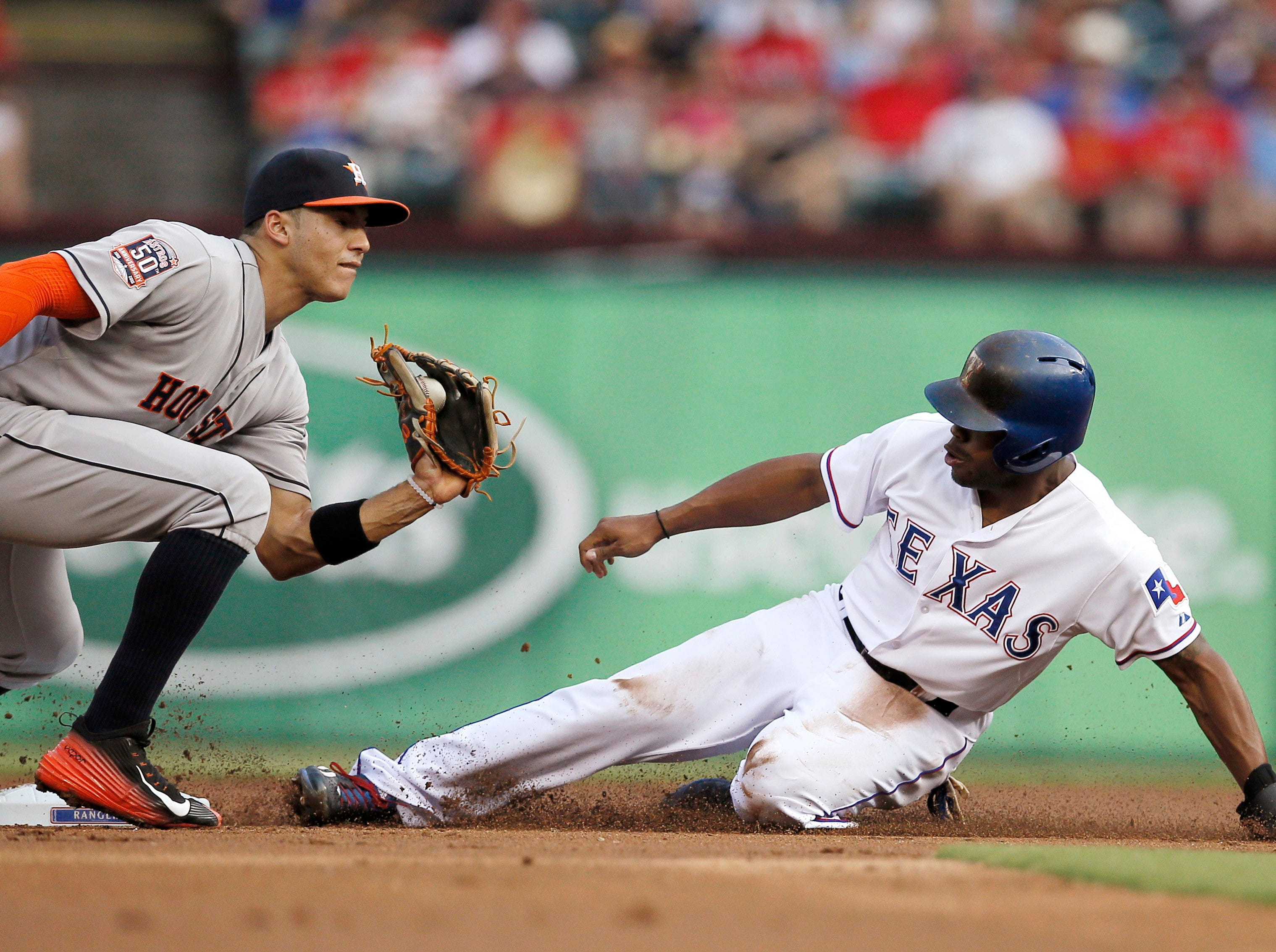 Houston Astros shortstop Carlos Correa is unable to tag Texas Rangers' Delino DeShields as DeShields steals second in the first inning of a baseball game Tuesday, Aug. 4, 2015, in Arlington, Texas. (AP Photo/Tony Gutierrez)