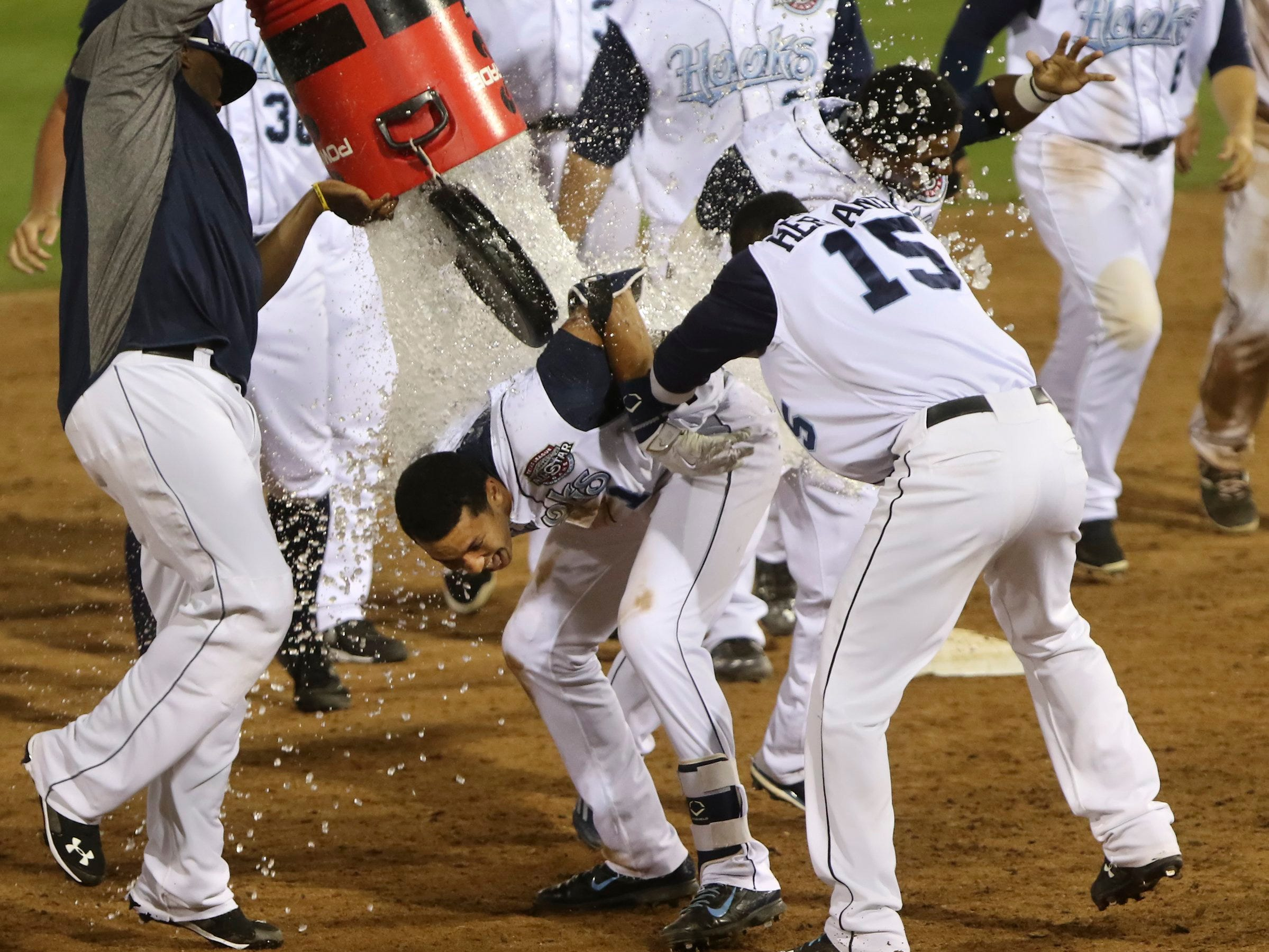 GEORGE TULEY/SPECIAL TO THE CALLER-TIMES Teoscar Hernandez (15) holds Carlos Correa for a traditional Gatorade bath following his ninth inning Three-RBI, Two-out, bases-loaded walk-off gapper to left center field for a 5-4 win over Frisco at Whataburger Field in Corpus Christi, Monday, May 4, 2015.