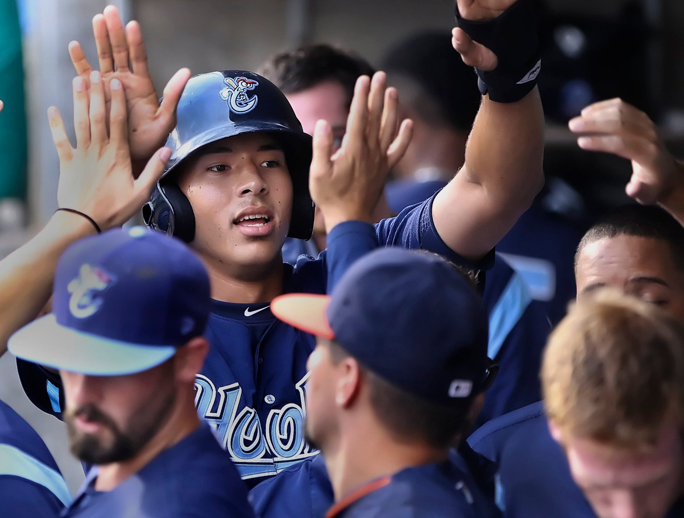 GEORGE TULEY/SPECIAL TO THE CALLER-TIMES Carlos Correa collects high fives in the dugout after scoring the Hooiks second run in the first inning for a 2-1 lead after his RBI double tied the game at Whataburger Field in Corpus Christi, Friday, April 17, 2015.