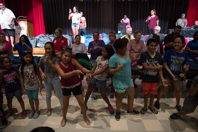 Kids take part in a dance-off during the 6th annual school supplies giveaway in the Robstown High School auditorium on Wednesday, Aug,1, 2018.