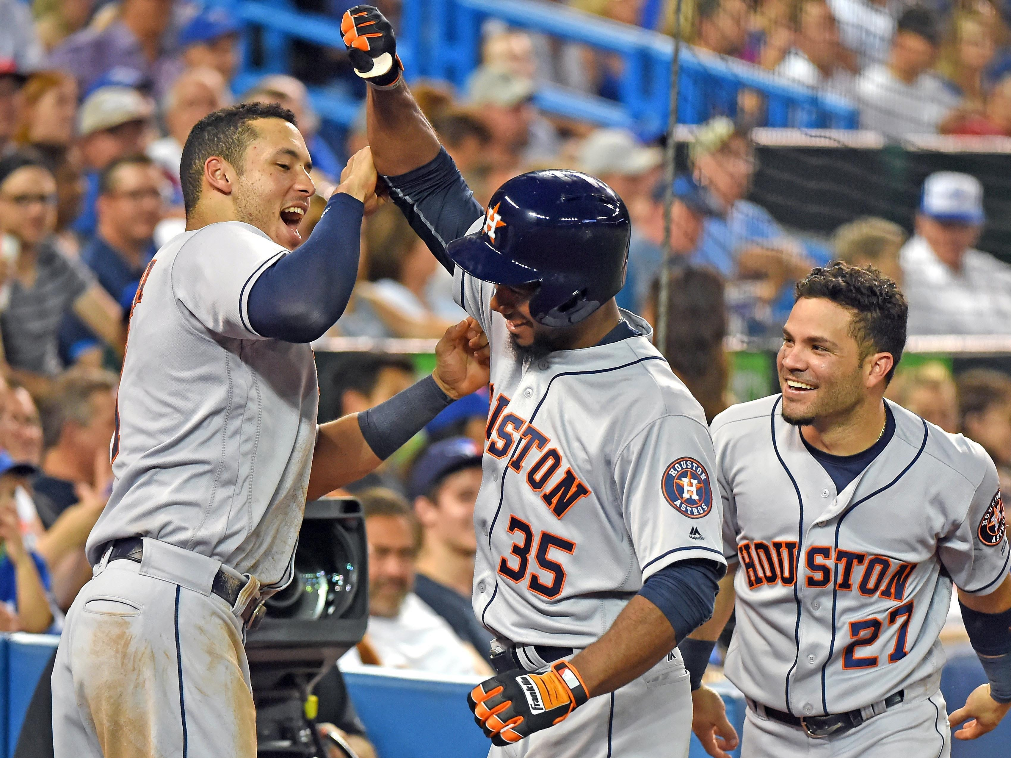 Aug 12, 2016; Toronto, Ontario, CAN;  Houston Astros center fielder Teoscar Hernandez (35) is greeted by shortstop Carlos Correa (1) and second baseman Jose Altuve (27) after hitting a home run in his major league debut against Toronto Blue Jays in the fifth inning at Rogers Centre. Mandatory Credit: Dan Hamilton-USA TODAY Sports