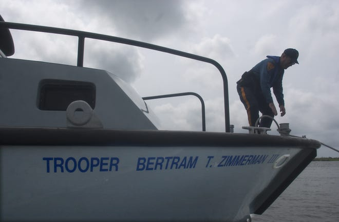 A New Jersey State Police station commander secures a police boat. The state police based at the Atlantic City Marine Services Station came to the rescue of a passenger with a medical emergency in Brigantine on Tuesday.
