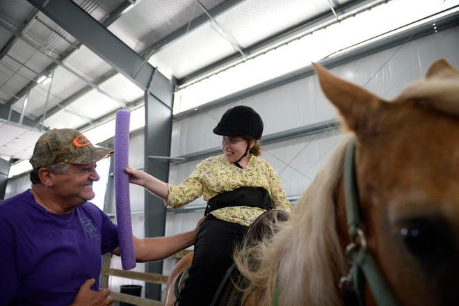 Kierstin Leigh Stump, 25, right, 'boops' volunteer Mike Reynolds with a noodle during a session at the Therapeutic Riding Center in Logan Township.