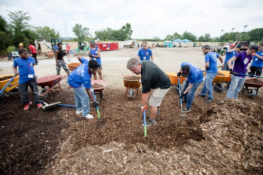 Volunteers move mulch during the Reds Community Fund and P&G makeover of New Prospect Baptist Church in Roselawn on Thursday, August 2, 2018. 400 volunteers from P&G, Reds, Kroger, Children's Hospital, and others.