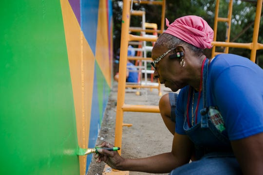 Kathy Troup, a New Prospect Baptist Church volunteer, paints on a mural during the Reds Community Fund and P&G makeover of the church grounds and building in Roselawn.