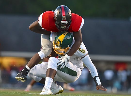 Mount Healthy's Lonnie Phelps Jr sacks Taft's Clevaland farmer during the Skyline Chili Crosstown Showdown, Thursday, August 24th at Mount Healthy High School