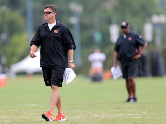 Cincinnati Bengals offensive coordinator Bill Lazor walks through a drill as Cincinnati Bengals head coach Marvin Lewis, background, looks on during Cincinnati Bengals training camp practice, Wednesday, Aug. 1, 2018, on the practice fields next to Paul Brown Stadium in Cincinnati.