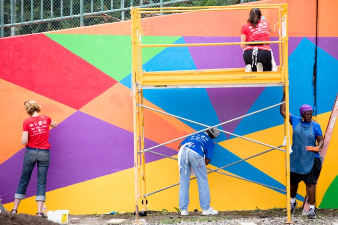 Volunteers paint on a mural during the Reds Community Fund and P&G makeover of New Prospect Baptist Church in Roselawn.