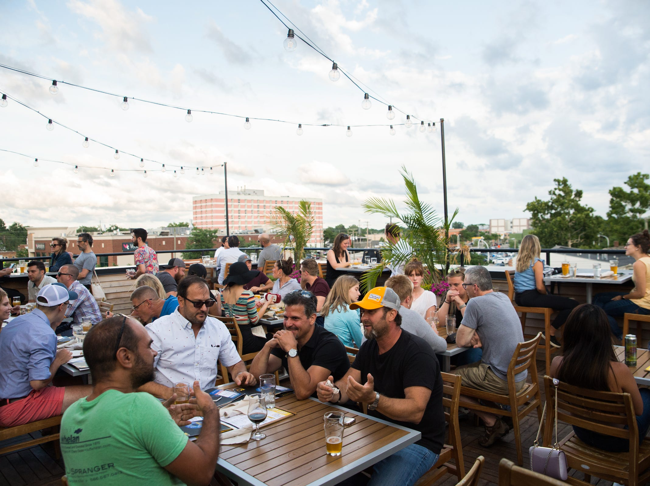 People converse on the third floor terrace of HopCat in Royal Oak on Friday, July 20, 2018.