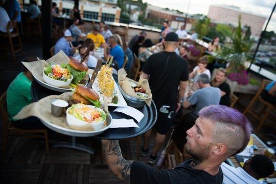 Kole Bishop of Berkley carries a tray of food to guests at HopCat in Royal Oak on Friday, July 20, 2018.