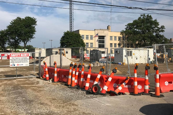 Barriers and fencing surround a construction site of an office tower planned for the former city parking lot in front of the Royal Oak City Hall, shown in the background, on August 1,2018.