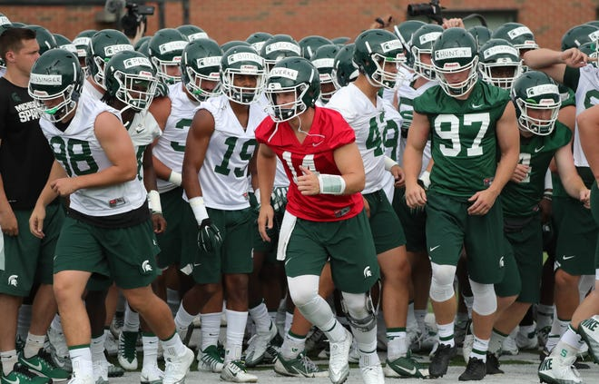 Michigan State quarterback Brian Lewerke leads the team onto the field during practice on Thursday, August 2, 2018, in East Lansing.