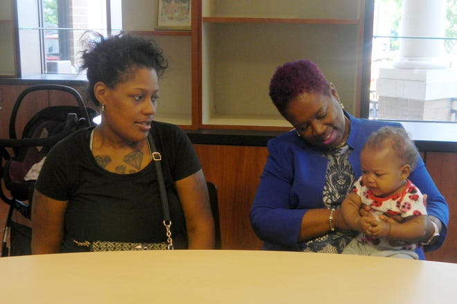 Danielle Works, 30, left and April Hill, 53, sit together as Hill holds Works' five-month-old daughter Hazel Brown. The two were  paired together through SisterFriends Detroit when Works was in her second trimester with Hazel.