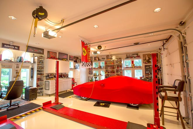 "A Ferrari 550 Maranello is under the red cover in this car lover's garage.Two garages, under a porte cochere, with three bays each, also hold a 1995 Viper and a yellow 2005 Ford GT, both of which he helped bring to the market. This garage is featured in the book ""Motor City Garages -- Amazing Collections From America's Greatest Car City."""