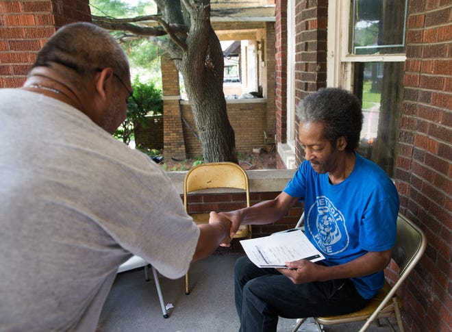 Leigh Bermea of Detroit speaks with Raford Perry of Detroit while canvassing on behalf of MOSES Action in Detroit on Aug. 2, 2018.